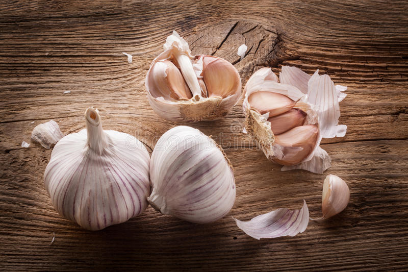 Garlic bulbs and cloves on wooden table royalty free stock photography