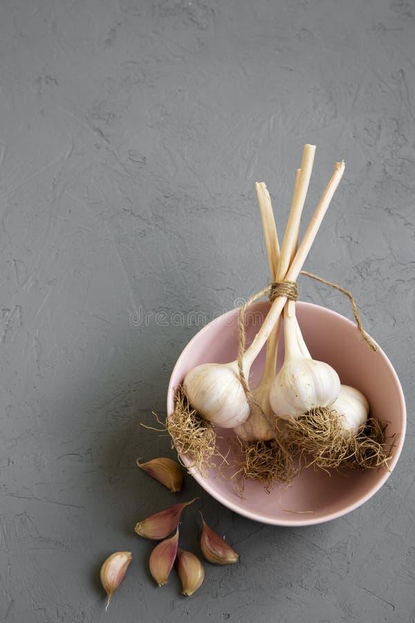 Garlic bulbs in pink bowl, garlic cloves over concrete background, top view. stock photos