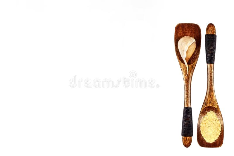 Garlic clove and garlic powder on a wooden spoon, isolated on white. Traditional aromatic spices. Medicinal spices. royalty free stock image