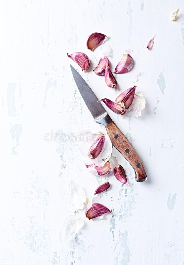 Garlic cloves and a kitchen knife royalty free stock image