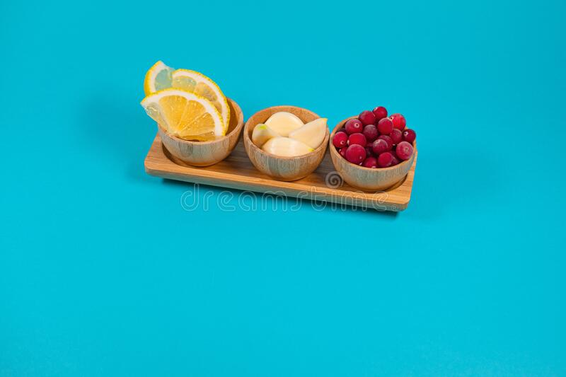 Garlic cloves, lemon slices and cranberries in a wooden dish.  stock images