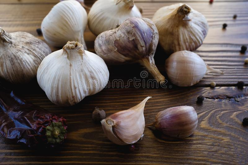 Garlic, garlic cloves and spices on a wooden table. Exquisite seasoning. Natural flavor. Antibacterial, boosts immunity. The. Concept of food, non-traditional royalty free stock image
