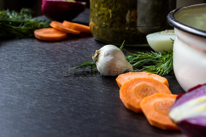 Garlic, dill, cut carrot, cut red onion, boiled egg near iron tureen and bowl of sorrel on dark wooden table. stock images