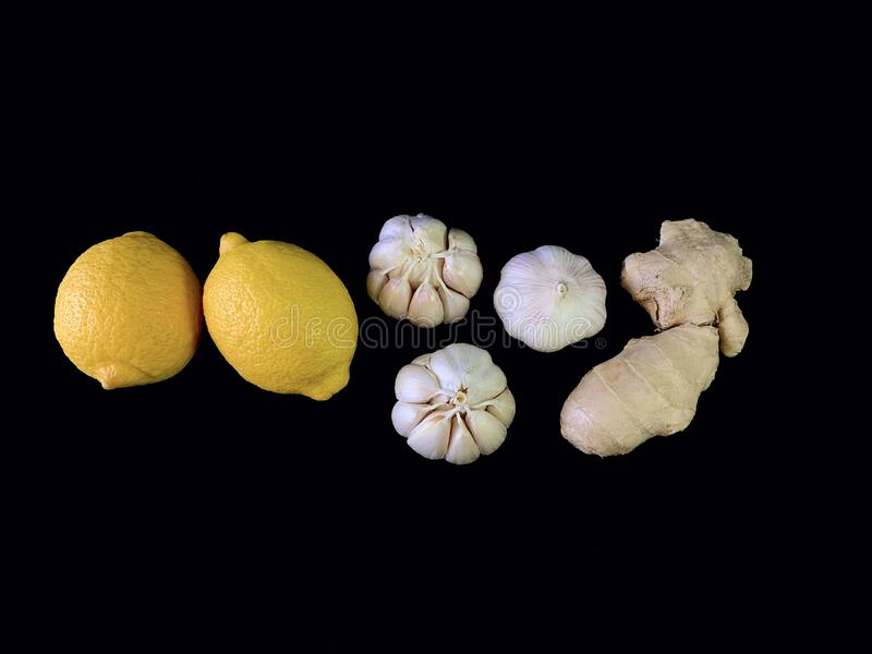 Garlic, ginger and lemon on a black background. Natural vitamins, antibiotics on a dark table. Concept: prevention of viral. Infections and corovirus at home royalty free stock images