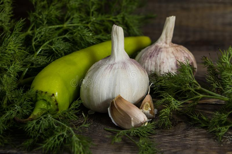Garlic, green hot pepper with dill on a wooden table. Vegetables stock photo