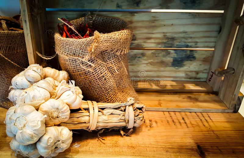 Garlic group and dry chilli in hemp sacks on the wooden table in the kitchen stock photo