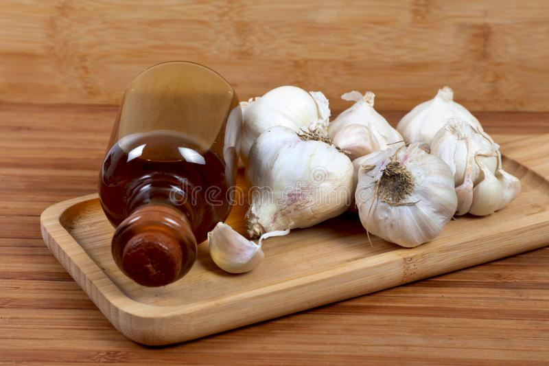 Garlic and oil. Beautiful shot of garlic and oil on wooden background stock image