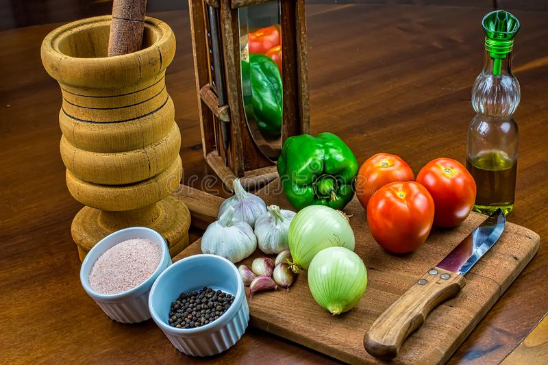 Garlic, onions, green peppers and tomatoes  on wooden cutting board with glass of olive oil, salt and black pepper in ramekins, wo royalty free stock photos