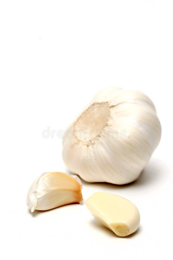 Garlic over white. Garlic in three stages, macro over white with shallow depth of field and focus on front clove stock photography