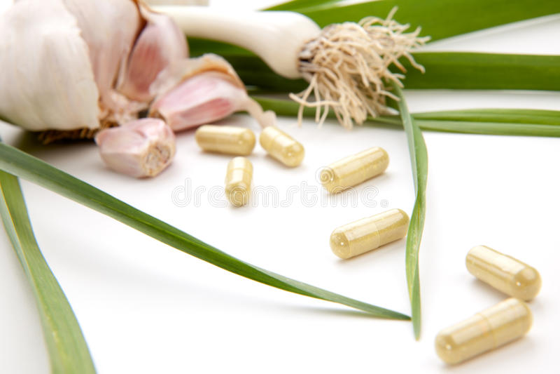 Garlic pills stock photography