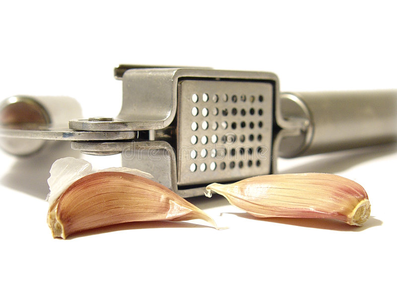 Garlic and press. Garlic cloves and stainless steel press isolated on a white background stock images