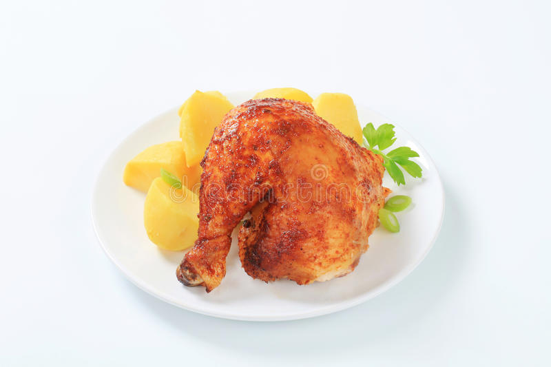 Garlic roasted chicken leg with potatoes stock photography