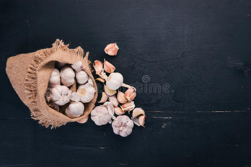 Garlic in a sack of old cloth. Fresh garlic on a wooden background. royalty free stock images