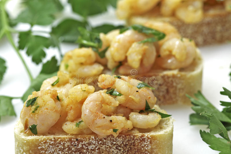 Garlic shrimp tapas on sourdough bread. Small shrimp dressed in a garlic, red pepper flake, ground pepper, and curry dressing presented on a slice of sourdough stock photos