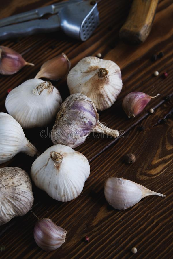 Garlic and spices on a wooden table. Cooking with garlic. Strengthening of immunity. Close-up, vertical shot.  stock image