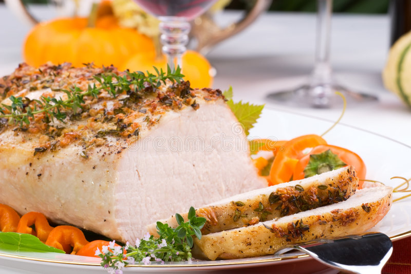 Garlic Thyme Roast Pork. Delicious sliced garlic thyme roast pork loin is ready for dinner in middle of fall arrangment table and two glasses of red wine stock photography
