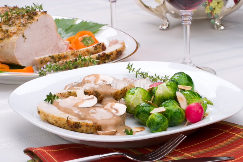 Garlic Thyme Roast Pork. Delicious sliced garlic thyme roast pork loin with mushrooms sauce, brussels sprouts, almonds and radish ready for dinner in middle of royalty free stock photos