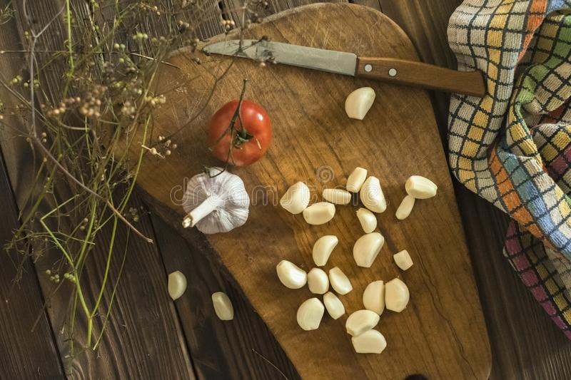 Garlic, tomato and coriander. Garlic cloves, tomato and coriander on a chopping Board. Knife and towel-all ready to cook royalty free stock photography