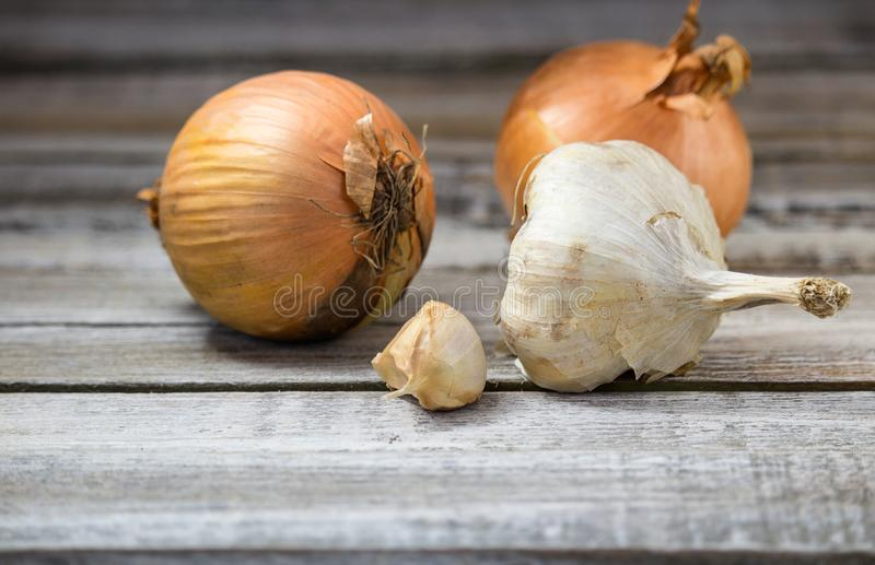 Garlic with two onion on rustic white wood royalty free stock photography