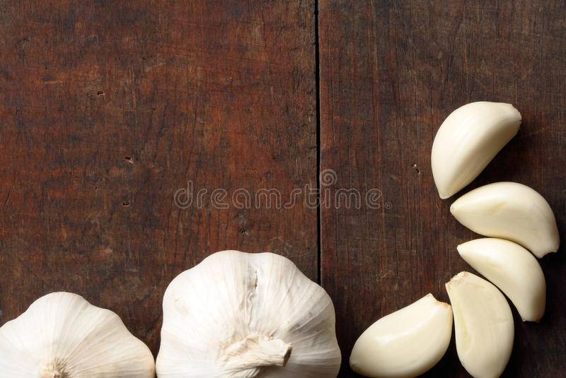 Garlic On Wood. Closeup od garlic lying on dark wooden background with copy space royalty free stock images