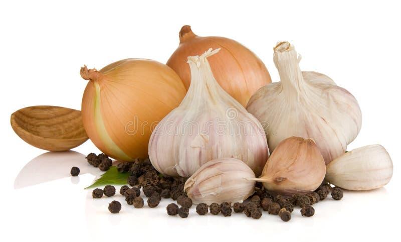 Garlics, pimienta y cebolla aislados en blanco imagenes de archivo