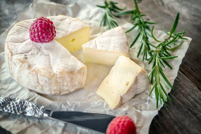 Garmażeryjny korzenny Camembert ser, brie z rozmarynami i malinka na pięknym textured drewnianym tle, zak?ska korzenna zdjęcie stock