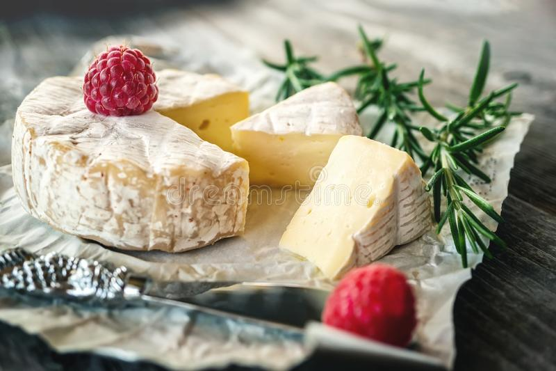 Garmażeryjny korzenny Camembert ser, brie z rozmarynami i malinka na pięknym textured drewnianym tle, zak?ska korzenna obraz stock