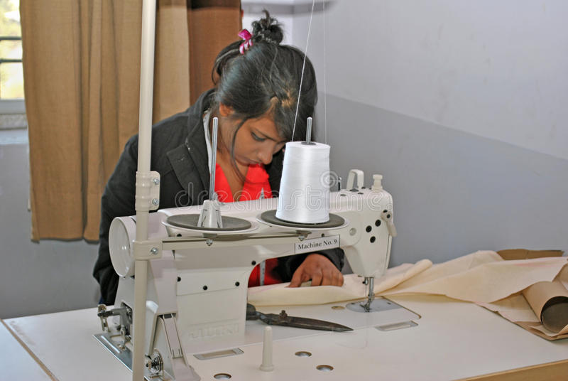Garment manufacturing workshop. A group of young Indian girl is busy with stitching garments with modern swing machines in a workshop in India. Fashion industry royalty free stock image