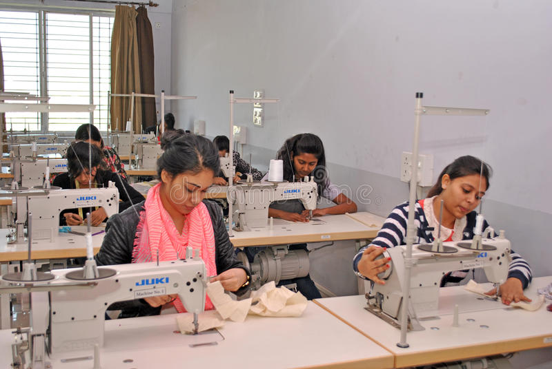 Garment manufacturing workshop. A group of young Indian girl is busy with stitching garments with modern swing machines in a workshop in India. Fashion industry royalty free stock images