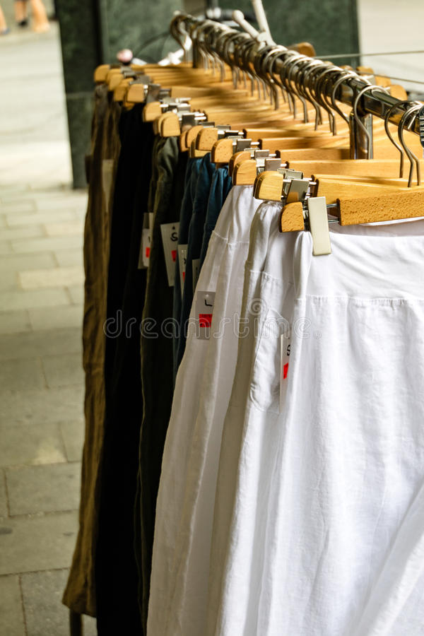 Garments hanging on a rail in a fashion boutique. On wooden hangers in a fashion, shopping, retail and consumerism concept stock photo
