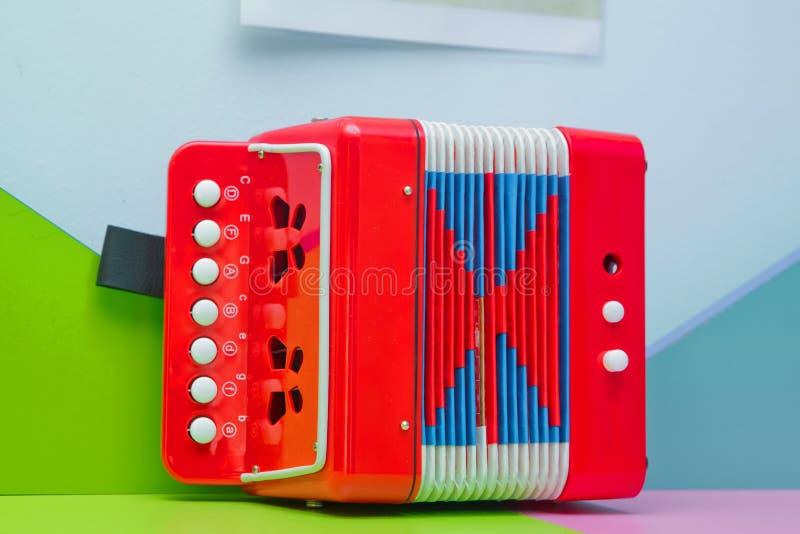 Garmon pequeno vermelho para crianças Um acordeão pequeno, harmônico, instrumento musical, chaves do branco do reparo da música i imagens de stock royalty free
