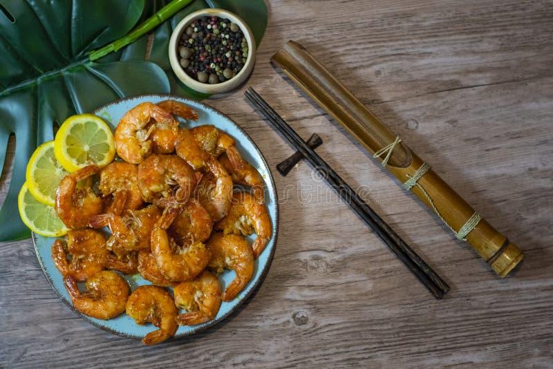 Garnalen in de zoete en kruidige hoogste mening van de saus Aziatische schotel met eetstokje op een houten lijst stock foto