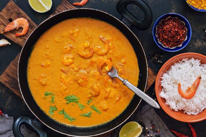 Garnalen met kerriesaus in een pan op een donkere achtergrond Thaise, Indische schotel Aziatisch Voedsel stock afbeelding