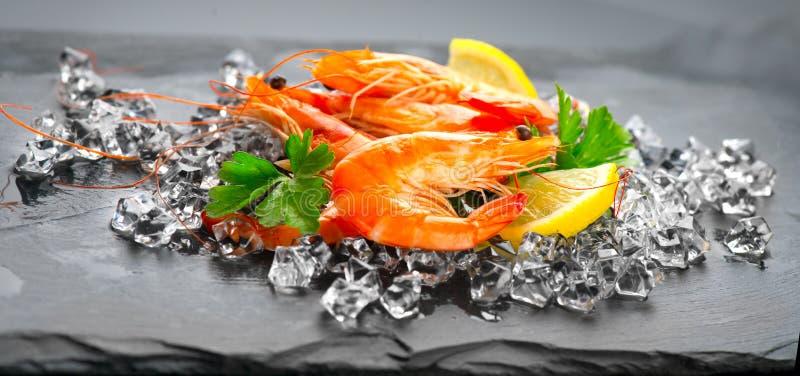 garnalen Verse garnalen op een zwarte achtergrond Zeevruchten op verpletterd ijs met kruiden Gezond voedsel stock fotografie
