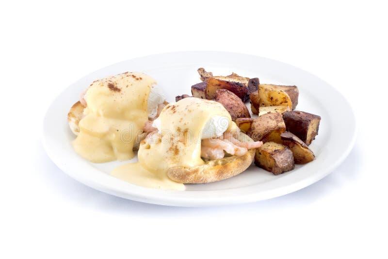 garnaleneieren Benedict met gebakken aardappelen stock foto