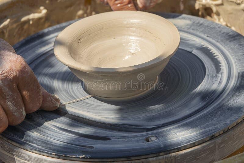 Garncarka ciie skończoną glinianą wazę od przędzalnianego koła Lato garncarki plenerowe lekcje fotografia royalty free
