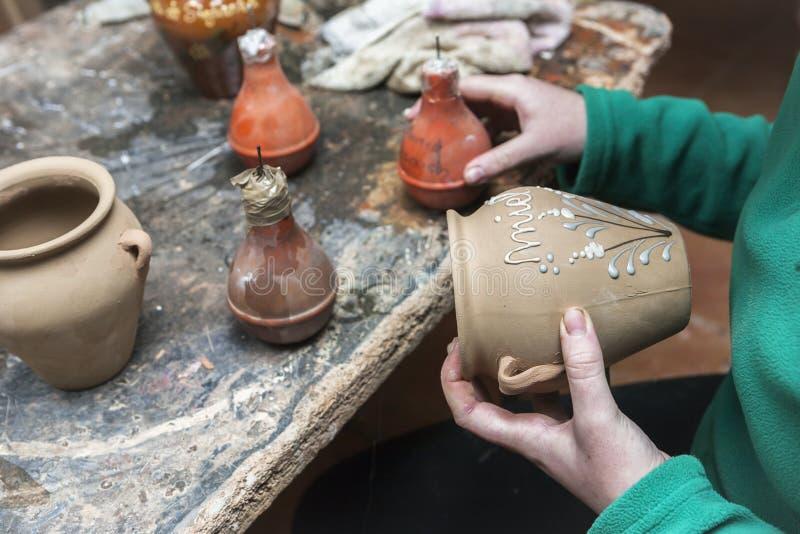 Garncarka dekoruje z emalią ceramics kawałek przed stawiać wewnątrz zdjęcia royalty free