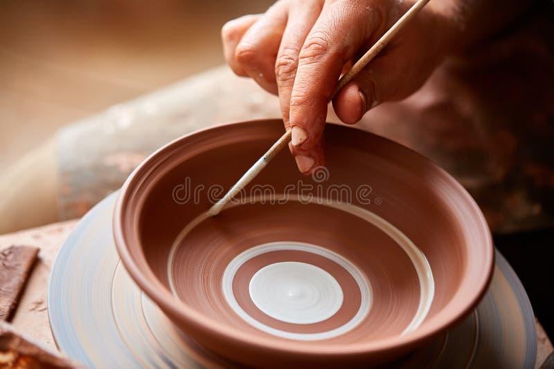 Garncarka maluje glinianego talerza w bielu w warsztatowym, odgórnym widoku, zakończenie, selekcyjna ostrość obrazy royalty free