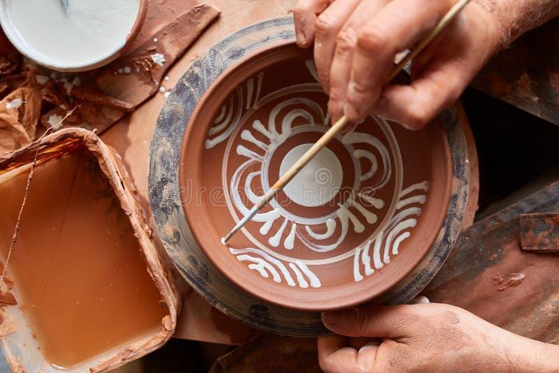 Garncarka maluje glinianego talerza w bielu w warsztatowym, odgórnym widoku, zakończenie, selekcyjna ostrość obrazy stock