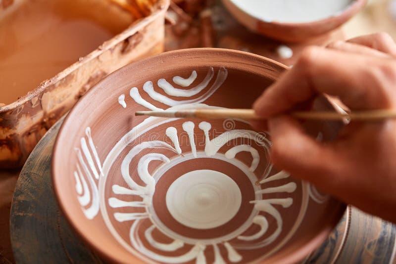 Garncarka maluje glinianego talerza w bielu w warsztatowym, odgórnym widoku, zakończenie, selekcyjna ostrość zdjęcia royalty free