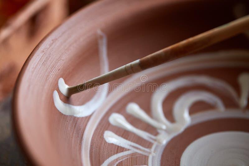 Garncarka maluje glinianego talerza w bielu w warsztatowym, odgórnym widoku, zakończenie, selekcyjna ostrość fotografia stock