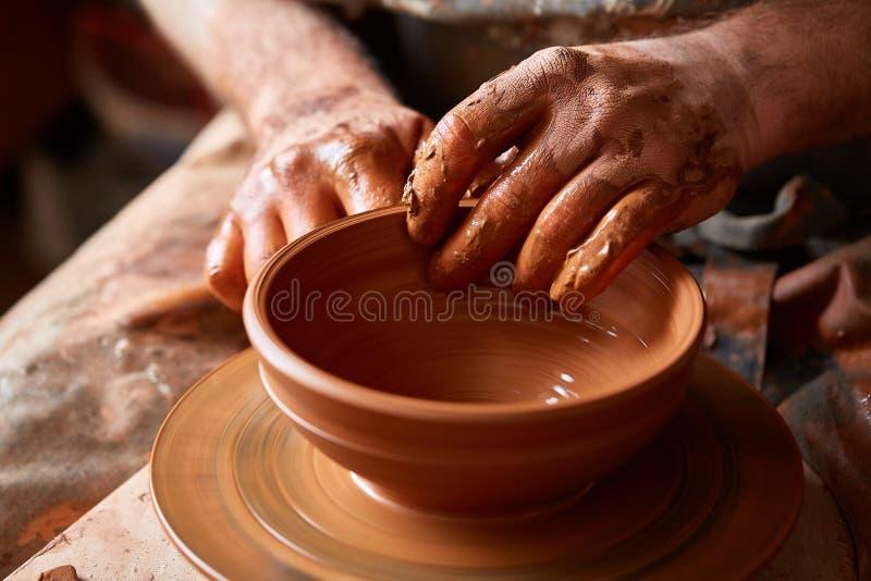 Garncarka maluje glinianego talerza w bielu w warsztatowym, odgórnym widoku, zakończenie, selekcyjna ostrość fotografia royalty free