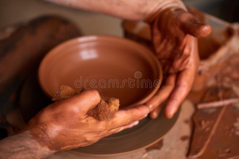 Garncarka maluje glinianego talerza w bielu w warsztatowym, odgórnym widoku, zakończenie, selekcyjna ostrość zdjęcia stock
