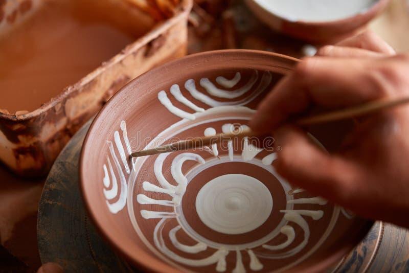 Garncarka maluje glinianego talerza w bielu w warsztatowym, odgórnym widoku, zakończenie, selekcyjna ostrość obraz stock