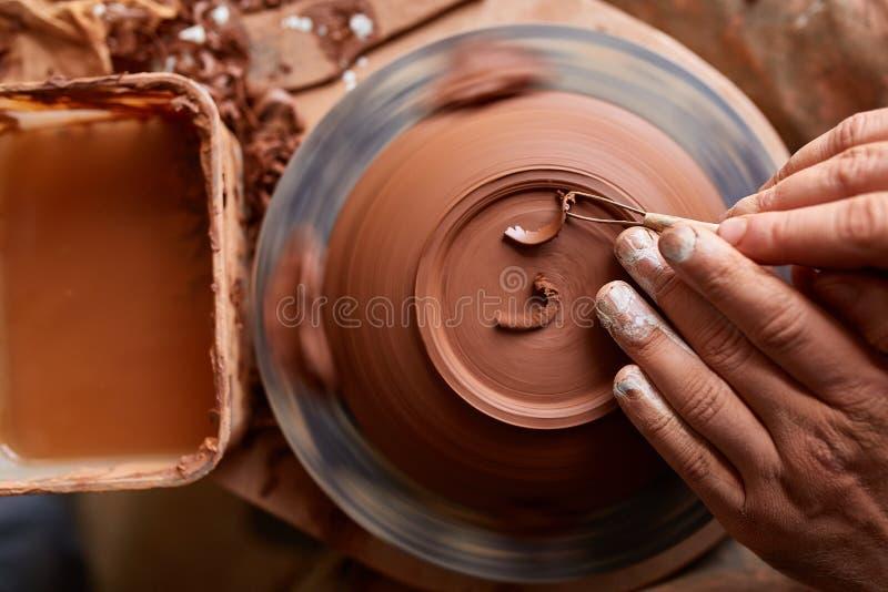 Garncarka maluje glinianego talerza w bielu w warsztatowym, odgórnym widoku, zakończenie, selekcyjna ostrość zdjęcie royalty free