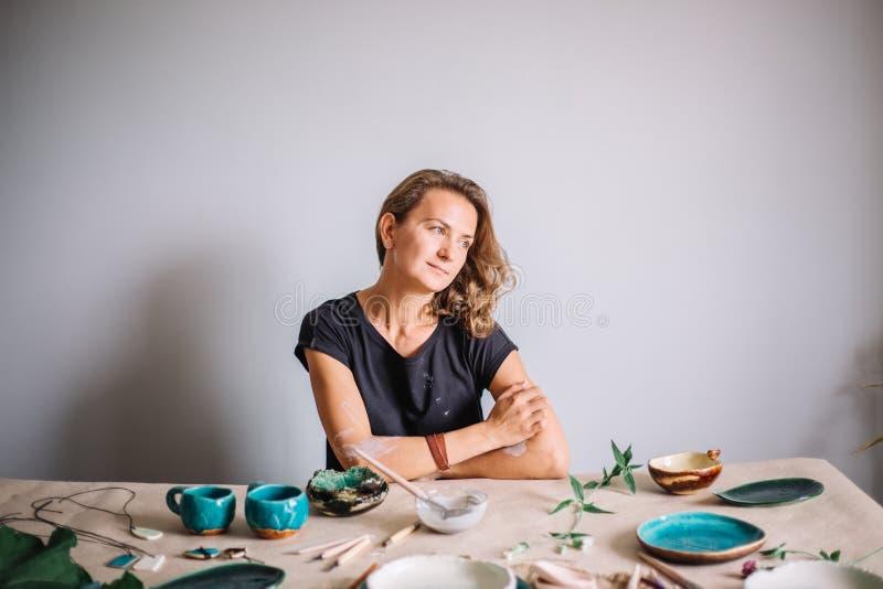 Garncarka, narzędzia, ceramics sztuki pojęcie - przystojny młody brunetki kobiety ono uśmiecha się zdjęcie stock