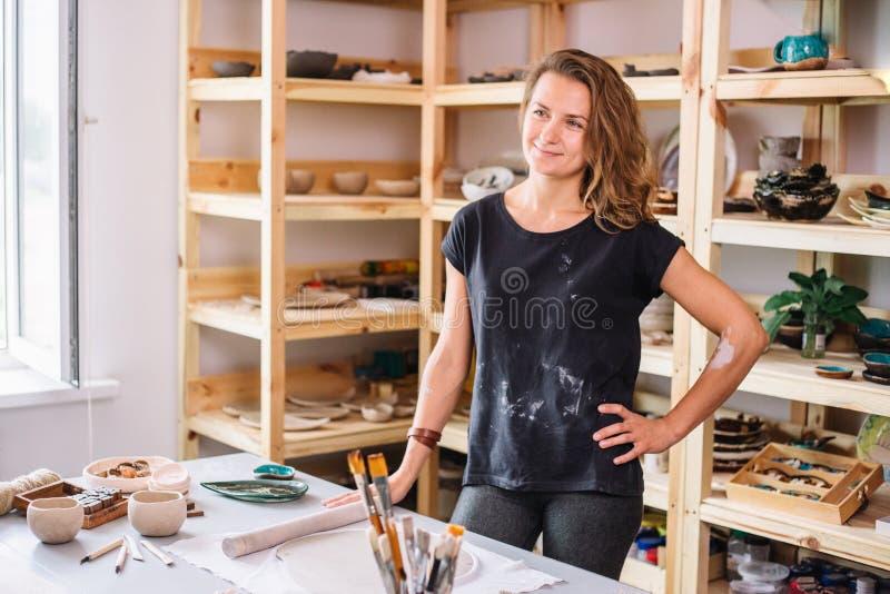 Garncarka, narzędzia, ceramics sztuki pojęcie - przystojny młody brunetki kobiety ono uśmiecha się zdjęcia stock