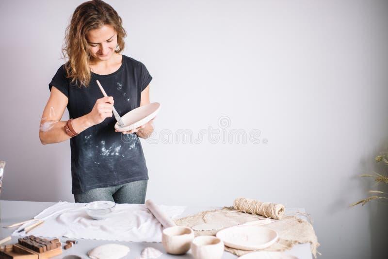 Garncarka pleśnieje filiżankę glina Młoda garncarka dekoruje filiżankę glina zdjęcie stock