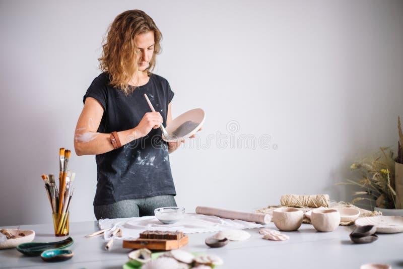 Garncarka pleśnieje filiżankę glina Młoda garncarka dekoruje filiżankę glina obrazy stock