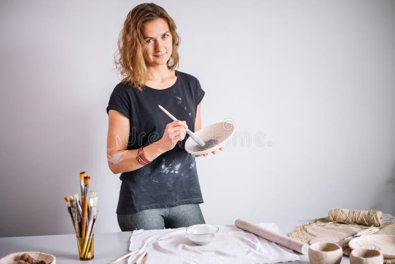 Garncarka pleśnieje filiżankę glina Młoda garncarka dekoruje filiżankę glina fotografia stock